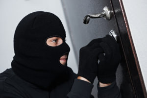 Thief Burglar force lock metal door with a tool during house breaking